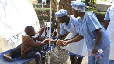 Health workers offer food to a father and son suffering from cholera symptoms at a local hospital in Harare on Tuesday.