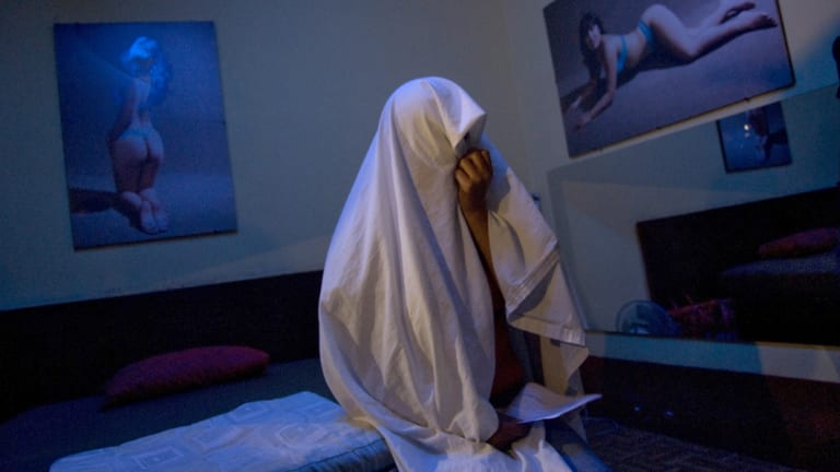 A prostitute covers herself with a sheet as she waits to receive a free HIV/AIDS test at a brothel in Callao, Peru.