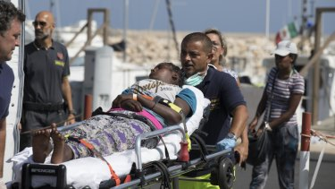 A woman is carried away on a stretcher after disembarking from an Italian Coast Guard ship in the port of Pozzallo, Southern Italy, on Sunday.
