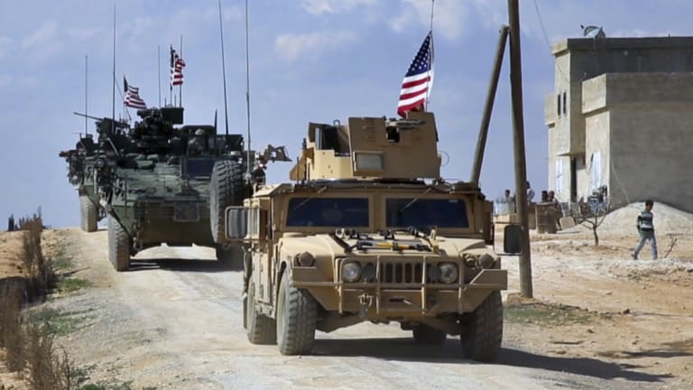 A frame grab from video provided by Arab 24 network shows U.S. forces patrol on the outskirts of the Syrian town Manbij.