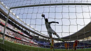 Full flight: Socceroos' goalkeeper Mat Ryan blocks a shot during the Group B opener against Jordan.