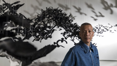 Cai Guo-Qiang with his installation of 10,000 porcelain birds.