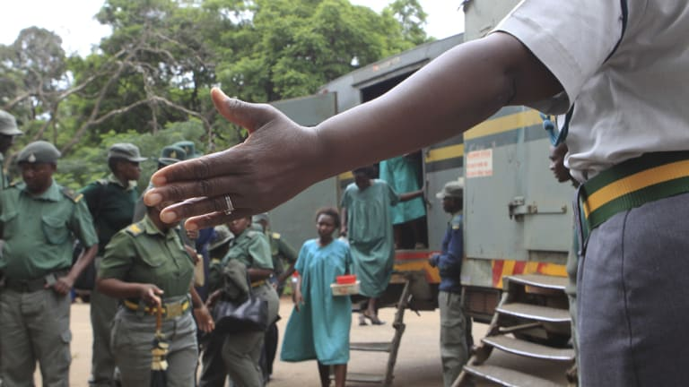 A prison guard directs some of the people arrested during protests as they arrive to make their magistrates court appearance on Thursday.