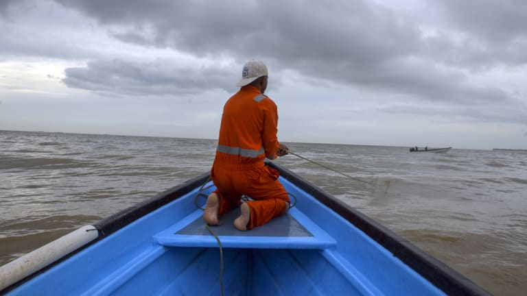 A fisherman  rides in a boat where some have been either robbed and/or killed by Venezuelan pirates.