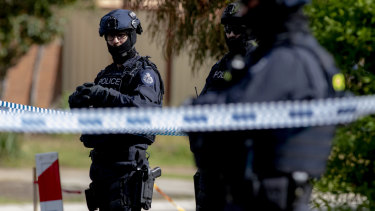 Police stand guard during a house raid in Werribee on Saturday following the Bourke Street attack.