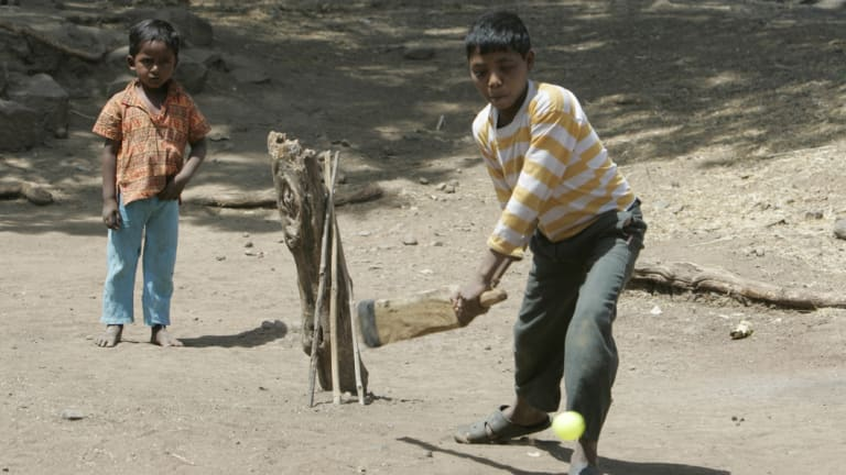 Village children play cricket in the street. Calls are growing for affirmative action to give more cricketers from a lower caste in India an opportunity to play for their country.