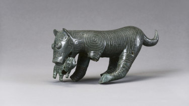 A bronze sculpture of a tiger mother with cub in its mouth from the Western Zhou Dynasty, 1046–771 BCE.