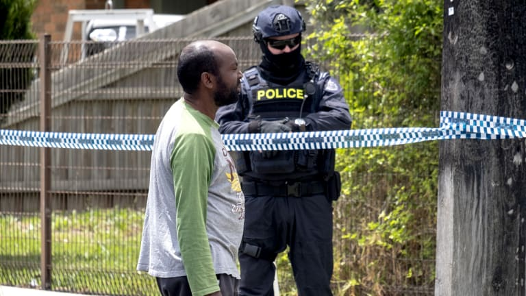 A family friend talks to police outside a house being raided in Werribee in connection to Hassan Khalif Shire Ali.