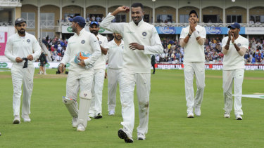 Ovation: Indian cricketers applaud teammate India's Hardik Pandya, holding the ball, after his five-wicket haul against England.