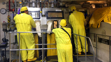 Workers in protective gear handle radioactive waste at Los Alamos National Laboratory.