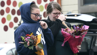 Unidentified people bring flowers to the scene where 20 people died when a limousine crashed into an car in Schoharie, New York.