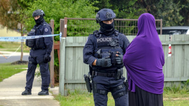 An armed police officer speaks to a woman as she arrives at the home of Shire Ali's parents in Werribee.