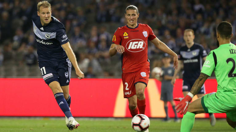 Ola Toivonen of the Victory puts the ball past Adelaide United goalkeeper Paul Izzo.