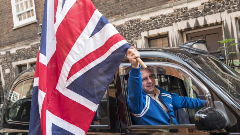 A taxi driver waves a Union Jack flag at Nigel Farage, a day after Britain voted to break out of the EU.