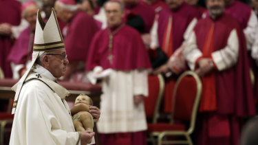 Pope Francis holds a statue of baby Jesus as he leaves at the end of the Christmas Eve Mass in St. Peter's Basilica.