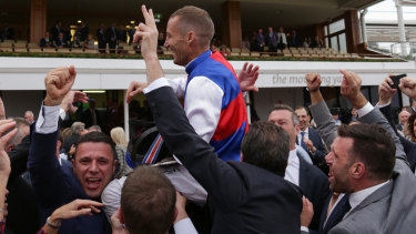 Jockey Damien Oliver is mobbed by winning owners after Steel Prince's narrow win on Saturday.