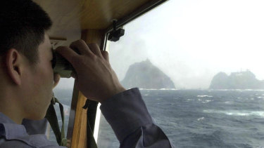 A South Korean coast guard looks at Dokdo islets, known as Takeshima in Japanese, from the patrol ship Sambong-ho on the East Sea, South Korea.