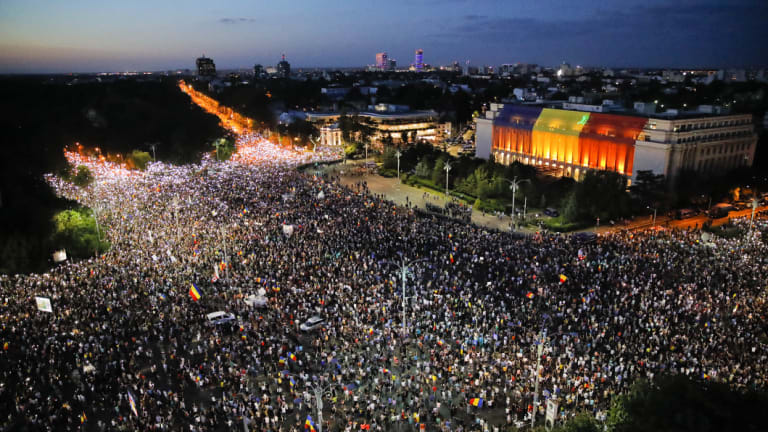 People shine the lights of their mobile phones during protests outside the government headquarters, seen at right.