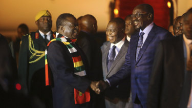 Zimbabwean President Emmerson Mnangagwa, left, is greeted as he arrives at Robert Mugabe International Airport in Harare on Monday.