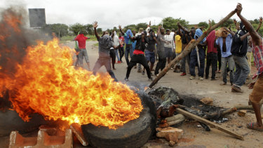 Protesters gather near a burning tyre during a demonstration over the rise in fuel prices in Harare, Zimbabwe, on Tuesday.