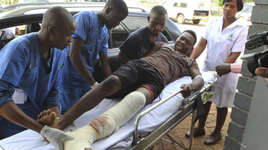 An injured man is helped at a private hospital after an alleged assault by a group of uniformed soldiers.