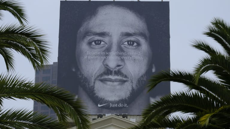 Palm trees frame a large billboard on top of a Nike store that shows former San Francisco 49ers quarterback Colin Kaepernick in San Francisco.