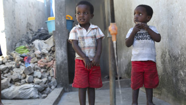 Children wait to fill up a bucket in Mozambique, where millions of people have been affected by Cyclone Idai.