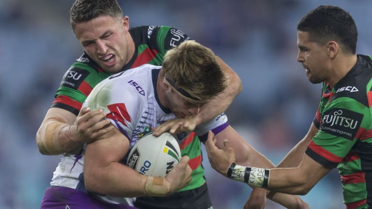 Sam Burgess of the Rabbitohs tackles Christian Welch of the Storm on Friday night.