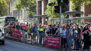 Sports fans crowd a tram stop at the corner of Collins and Spencer streets.