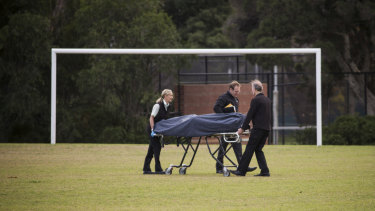 Police remove a woman's body from a Princes Park oval.
