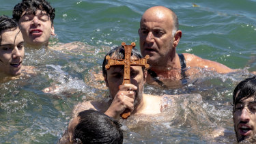 Dozens of men took part in the swim for the wooden cross tossed into Port Phillip Bay.