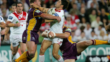 Trent Barrett (centre) is stopped by Shane Webcke and Brad Thorn during the NRL playoffs in 2006.