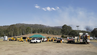 Fire and emergency crews from NSW prepare to join their Queensland counterparts in the ongoing bushfire control effort near the rural town of Canungra.