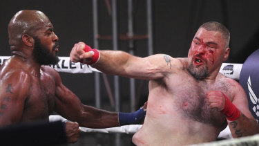Worse for wear: DJ Linderman (right) fights on with nasty cuts in his bare knuckle defeat by Arnold Adams.