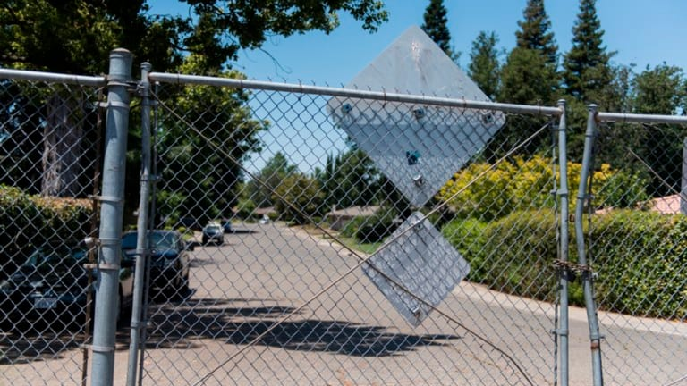 The levee behind this fence led to areas of thick brush and the American River, which the suspect often used to make his escape.