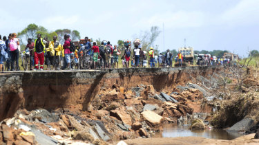 People pass through a section of the road damaged by Cyclone Idai in Nhamatanda in Mozambique.