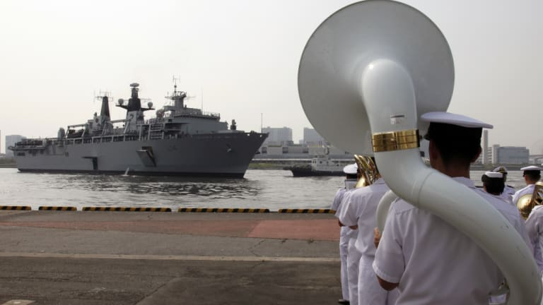 Japan Self-Defence Forces marching band members perform as British Royal Navy's HMS Albion amphibious assault ship arrives at a dock in Tokyo.
