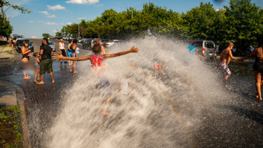 People stand in the spray of water coming from a fire hydrant in the Bronx borough of New York.