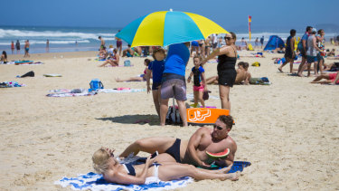 Swimmers and sunbakers bask in hot weather on the Gold Coast beaches.
