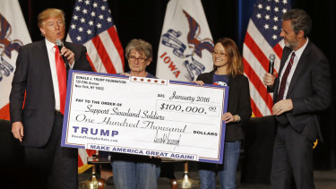 Donald Trump, left, stages a check presentation with an enlarged copy of a $100,000 contribution from the Donald J. Trump Foundation to Support Siouxland Soldiers during a campaign event in Sioux City, Iowa., during Trump's run for president. New York Attorney General Barbara Underwood filed a lawsuit accusing Trump of illegally using his charitable foundation to pay legal settlements and campaign costs.