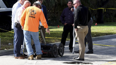 FBI and local police look at what authorities initially thought was a strange pothole in a suburban Florida street.