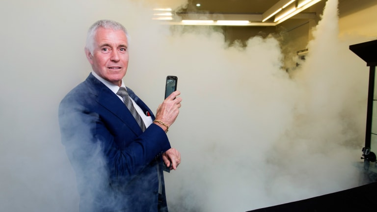 Jeweller Garry Holloway tests his smoke security system.