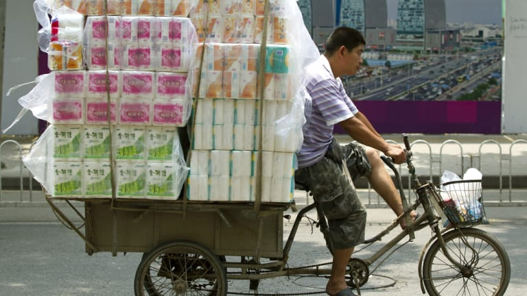 A tricycle porter transports packs of toilet paper in Beijing.