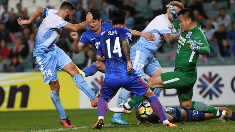 Shanghai goalkeeper Qiu Shengjiong and his teammates manage to block Alex Brosque.