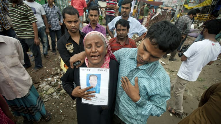 A woman holds a picture of her son, who went missing in the Rana Plaza building collapse in 2013 in Bangladesh.