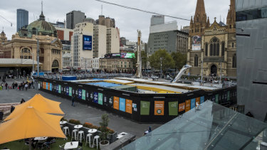 The tourist information centre booth at Federation Square has made way for the entrance to a new rail station being built as part of the Metro Tunnel project.