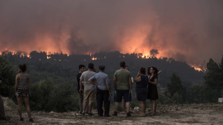 People observe as fire gets closer to the village of Monchique, Algarve, Portugal.