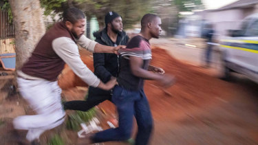 Nigerian foreign nationals remove a looter from their shops in Troyville, Johannesburg, and take him to a waiting police van on Monday.