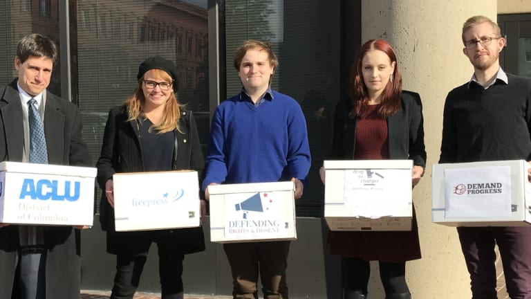 Michael Webermann and Elizabeth Lagesse, first and second from right, join Scott Michelman of the ACLU, far left, to hand in a petition urging the US Attorney's office to drop charges against the accused in the J20 case.