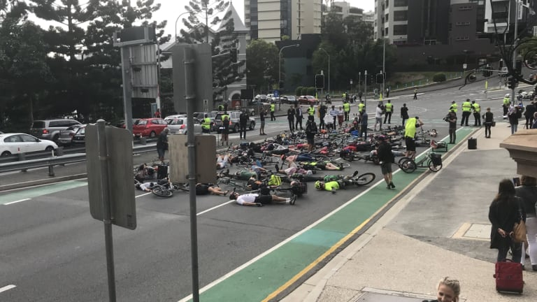 """Cyclists stage the """"die-in"""" protest during Brisbane's peak hour traffic."""